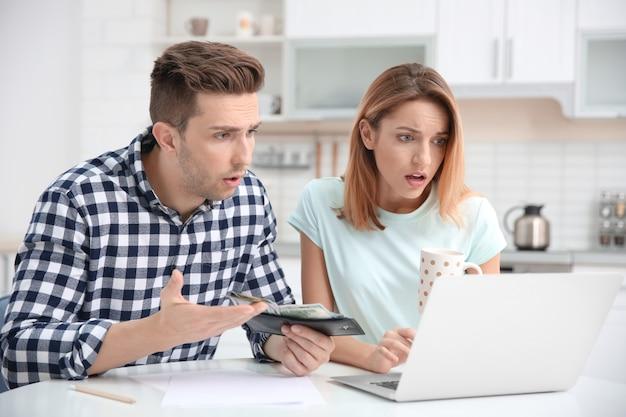 Młoda para zarządzająca rodzinnym budżetem w domu