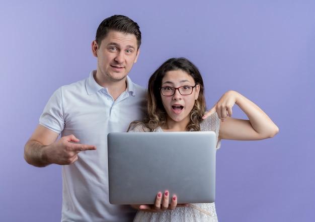 Młoda para zaskoczona kobieta hlding laptop wskazując palcem na to obok swojego chłopaka na niebiesko