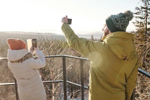 Młoda para ze smartfonami fotografująca przyrodę w zimowy dzień