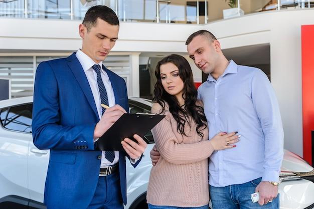 Młoda para ze sprzedawcą w pobliżu umowy podpisania nowego samochodu