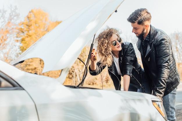 Młoda para zepsuła samochód podczas podróży w drodze na odpoczynek.