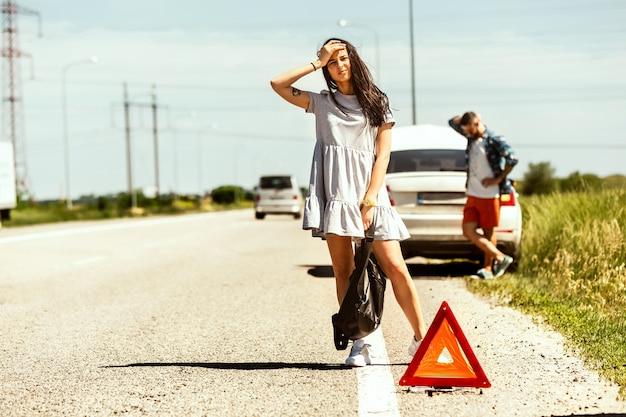 Młoda para zepsuła samochód w drodze na odpoczynek. próbują zatrzymać innych kierowców i poprosić o pomoc lub autostop. związek, kłopoty w drodze, wakacje.