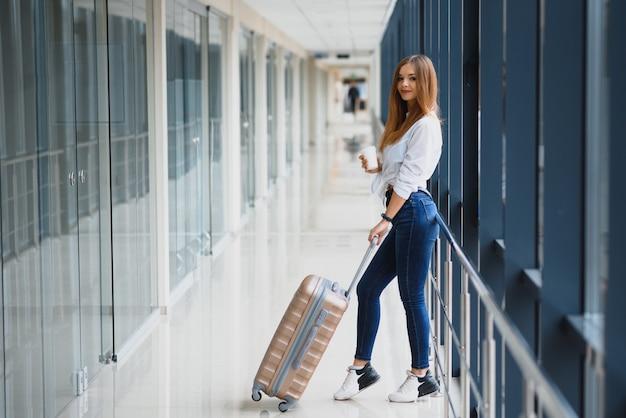 Młoda pasażerka na lotnisku, rozpaczliwie czekająca na opóźniony lot