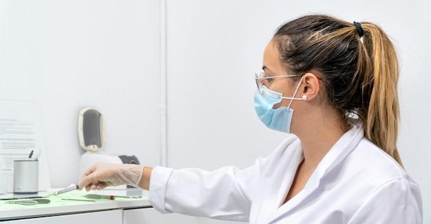 Młoda pedolog podczas chiropraktyki bierze swoje narzędzia ze stołu roboczego