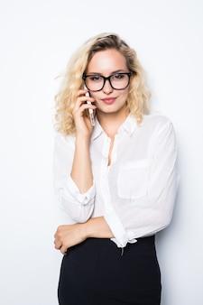 Młoda pewna kobieta rozmawia przez telefon komórkowy na białym tle