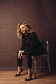 Młoda pewna kobieta siedzi na krześle na szarym tle.