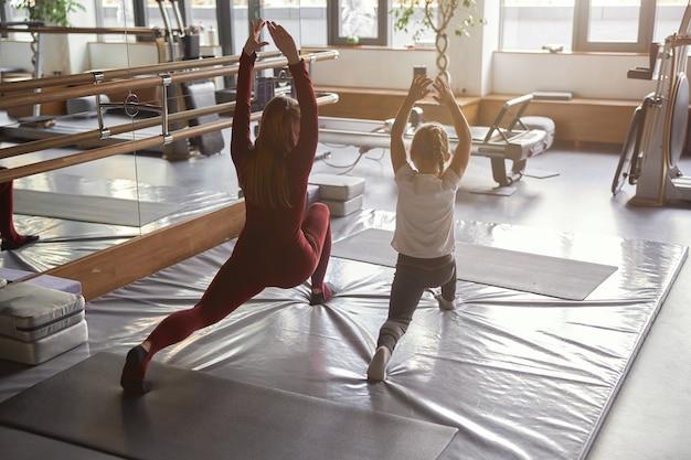 Młoda pewna nauczycielka pomaga dziewczynie z rozciąganiem w nowoczesnej sali
