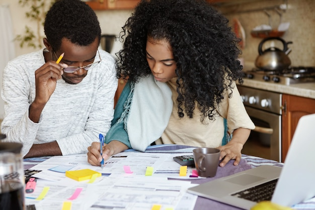 Młoda pewna siebie afrykańska gospodyni domowa z fryzurą afro pomaga mężowi w zarządzaniu finansami domowymi, kalkuluje i robi notatki piórem, siedząc przy kuchennym stole z laptopem i papierami