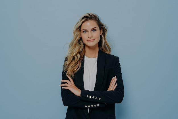 Młoda pewna siebie blond kobieta z długimi falującymi włosami, ubrana w elegancki czarny kostium stojący ze skrzyżowanymi rękami, pozowanie na niebieskim tle w studio z miejscem na kopię na reklamę