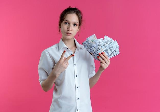 Młoda pewna siebie blondynka rosjanka gesty ręką znak zwycięstwa trzyma pieniądze na różowo z miejsca na kopię