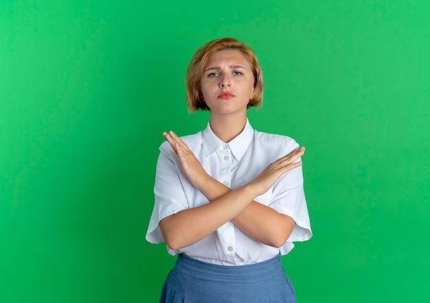 Młoda pewna siebie blondynka rosjanka krzyżuje ramiona, gestykulując nie na białym tle na zielonym tle z miejsca na kopię