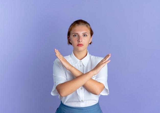 Młoda pewna siebie blondynka rosjanka krzyżuje ramiona, gestykulując nie na fioletowym tle z miejsca na kopię