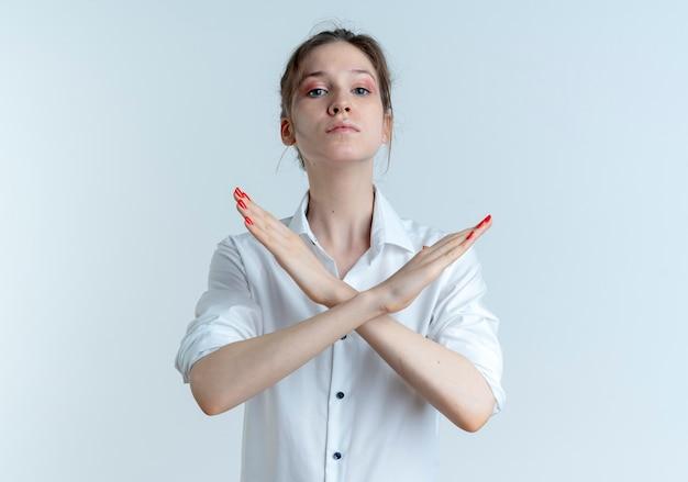 Młoda pewna siebie blondynka rosjanka krzyżuje ręce, gestykulując nie na białym tle z miejsca na kopię