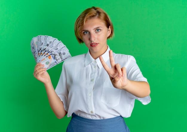 Młoda pewna siebie blondynka rosjanka trzyma pieniądze i gesty dwa palcami odizolowanymi na zielonej przestrzeni z miejsca na kopię