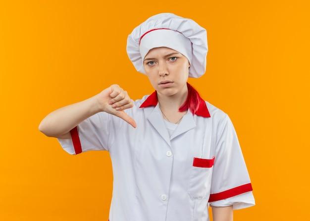 Młoda pewna siebie blondynka szefa kuchni w mundurze szefa kuchni kciuki w dół i wygląda na białym tle na pomarańczowej ścianie