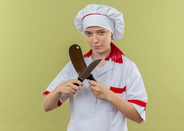 Młoda pewna siebie blondynka szefa kuchni w mundurze szefa kuchni przecina noże i wygląda na białym tle na zielonej ścianie