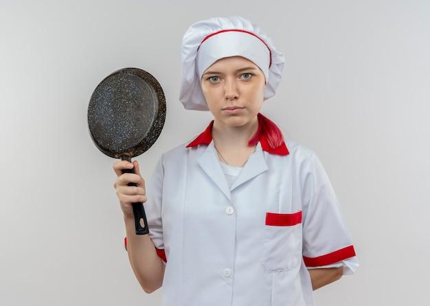 Młoda pewna siebie blondynka szefa kuchni w mundurze szefa kuchni trzyma patelnię i trzyma rękę za na białym tle na białej ścianie