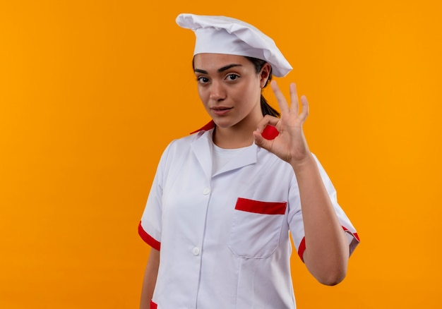 Młoda pewna siebie dziewczyna kaukaska kucharz w mundurze szefa kuchni gestykuluje znak ręką ok na pomarańczowej ścianie z miejsca na kopię