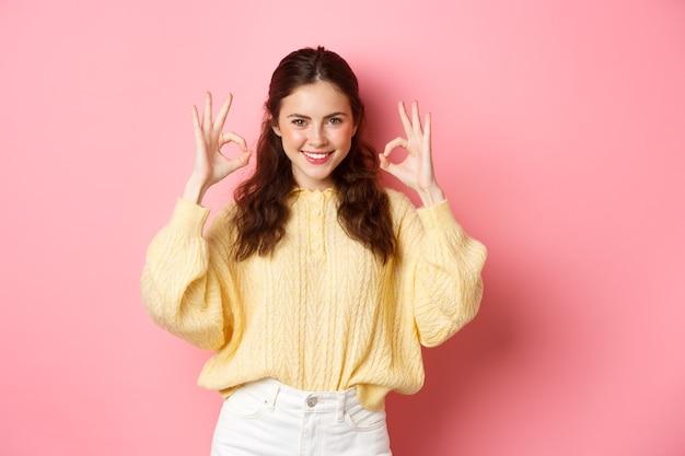 """Młoda pewna siebie dziewczyna pokazująca dobre znaki i uśmiechająca się, chwaląca coś idealnego, powiedz """"tak"""" lub """"w porządku"""", gest zatwierdź wybór stojąc nad różową ścianą"""