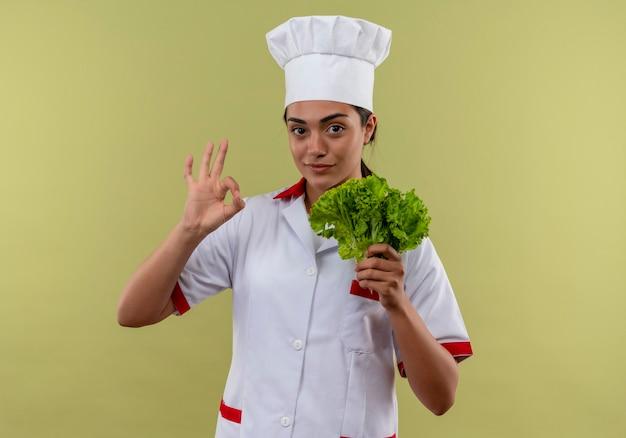 Młoda pewna siebie kaukaska kucharz dziewczyna w mundurze szefa kuchni trzyma sałatkę i gesty ok znak ręką na białym tle na zielonej ścianie z miejsca na kopię