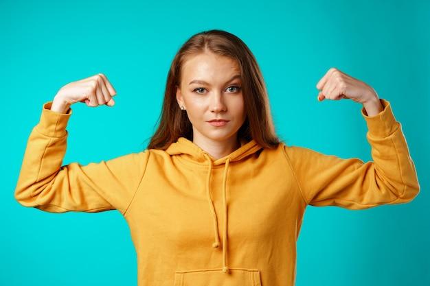Młoda pewna siebie kobieta pokazująca swoje silne ramiona