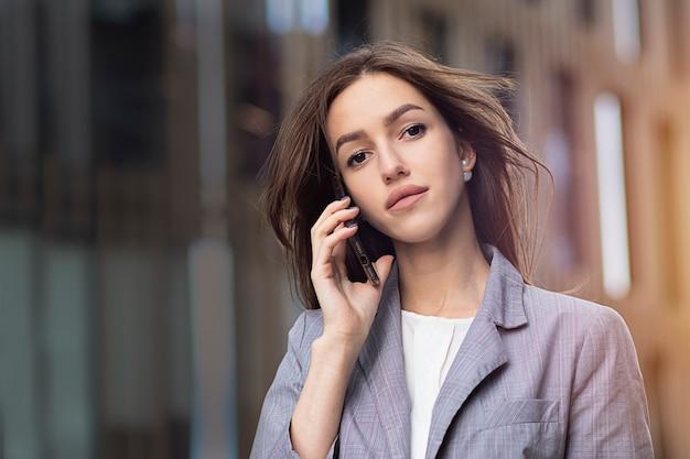 Młoda, pewna siebie kobieta rozmawia przez telefon komórkowy. kobieta jest oficjalnie ubrana, kobieta biznesu rozmawia przez telefon komórkowy.