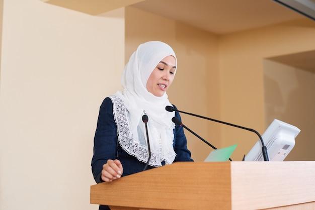 Młoda, pewna siebie muzułmańska bizneswoman w garniturze i hidżabie czyta punkty jej raportu trybuna przed publicznością
