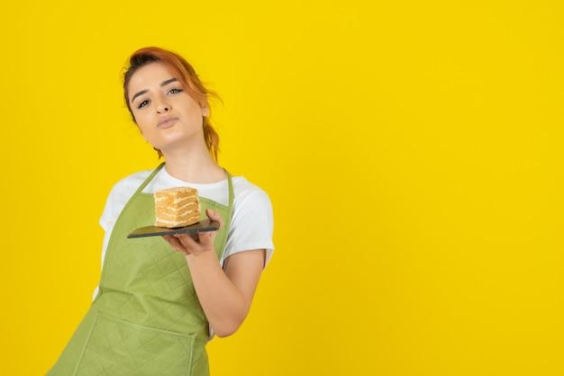 Młoda pewna siebie ruda trzyma kawałek ciasta na żółtej ścianie