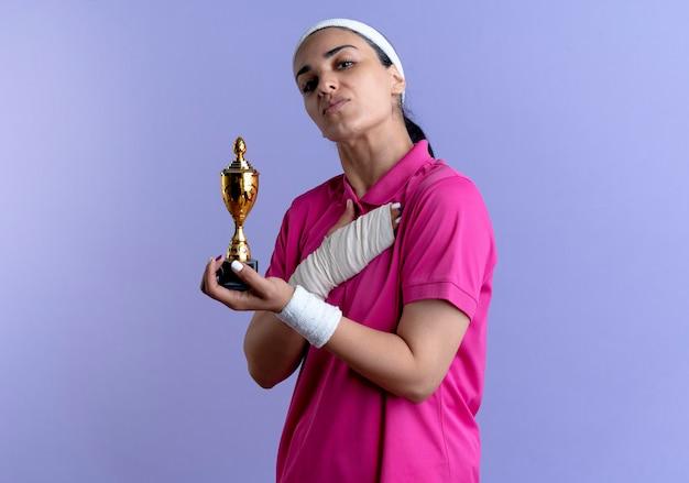Młoda, pewna siebie, sportowa kobieta kaukaska nosząca opaskę i opaski na rękę trzyma puchar zwycięzcy i kładzie rękę na klatce piersiowej odizolowanej na fioletowym tle z miejscem na kopię