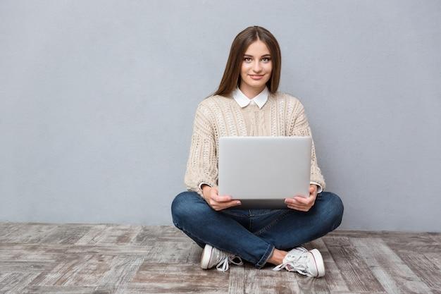 Młoda, pewna siebie, szczęśliwa uśmiechnięta kobieta korzystająca z laptopa siedzącego na drewnianej podłodze