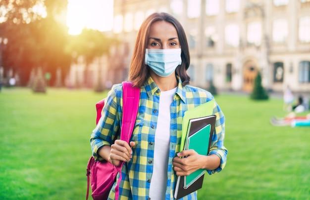 Młoda pewna studentka kobieta w ochronie maski medycznej z książkami i dokumentami w rękach i stojąc na kampusie uniwersyteckim