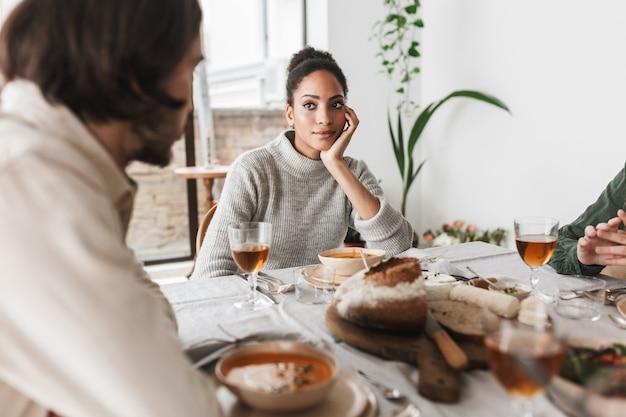 Młoda piękna african american kobieta z ciemnymi kręconymi włosami siedzi przy stole, opierając się na dłoni w zamyśleniu