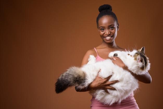 Młoda piękna afrykańska kobieta zulusów trzyma kota podczas uśmiechu