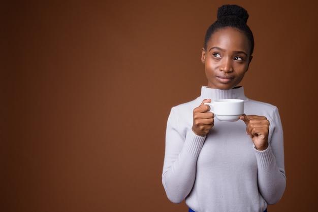 Młoda piękna afrykańska kobieta zulusów trzymając filiżankę kawy podczas myślenia