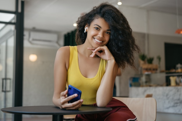 Młoda piękna amerykanin afrykańskiego pochodzenia kobieta słucha muzyka używać bezprzewodowych hełmofony