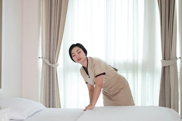 Młoda piękna asia pokojówka układa koc na łóżku w pokoju hotelowym