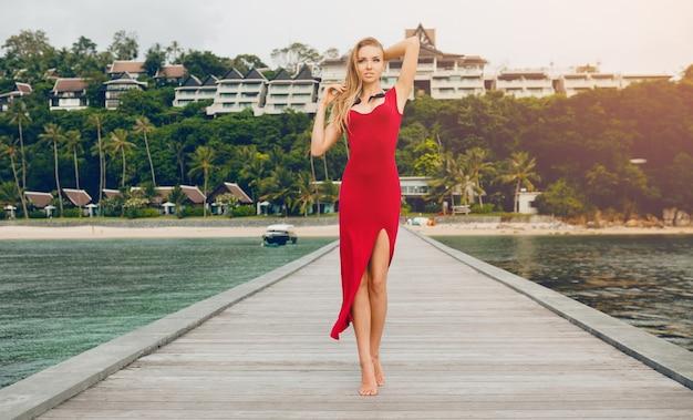 Młoda piękna atrakcyjna kobieta stojąca samotnie na molo w luksusowym hotelu, wakacje, czerwona długa sukienka, blond włosy, seksowna odzież, tropikalna plaża, uwodzicielska, zmysłowa, uśmiechnięta