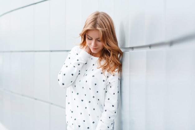 Młoda piękna atrakcyjna kobieta w stylowych wiosennych ubraniach stoi i marzy w pobliżu białej ściany w pomieszczeniu
