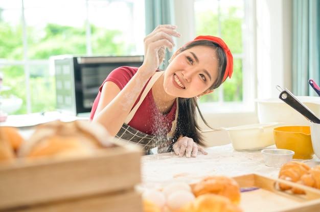Młoda piękna azjatka piecze w swoim biznesie w kuchni, piekarni i kawiarni