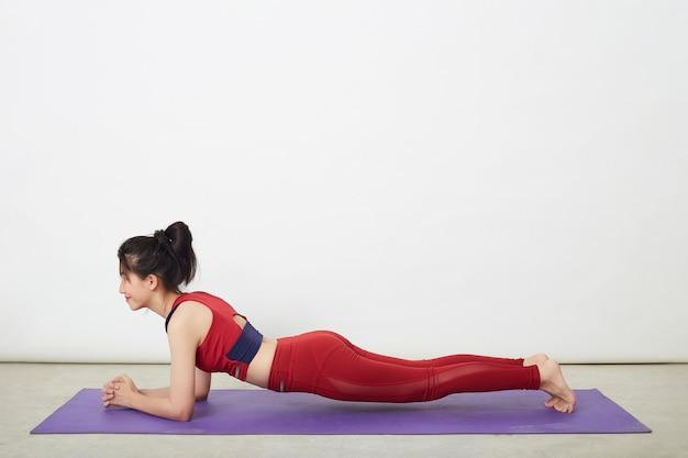 Młoda piękna azjatka robi kobrę pozę na macie do jogi w domu, koncepcja zdrowego życia i naturalnej równowagi między ciałem a rozwojem umysłowym