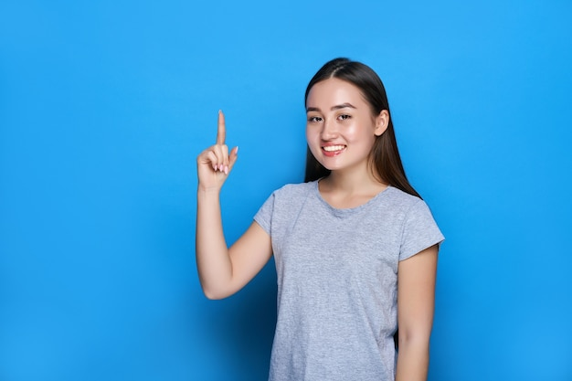 Młoda piękna azjatka uśmiecha się i pokazuje kciuki na niebieskiej ścianie