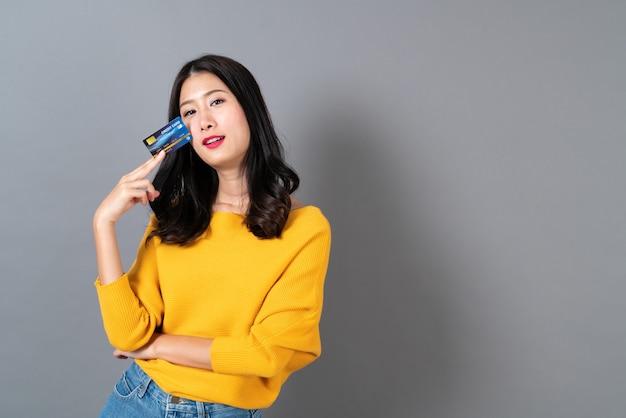Młoda piękna azjatka uśmiecha się i przedstawia w ręku kartę kredytową, pokazując zaufanie i pewność przy dokonywaniu płatności na szaro