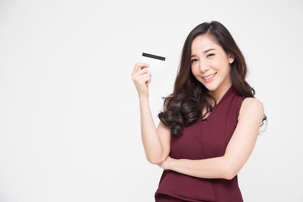 Młoda piękna azjatka uśmiecha się, pokazuje, przedstawia kartę kredytową do dokonywania płatności lub płacenia w internecie, zapłaci kupcowi lub jako zaliczkę na towary, posiadacza karty lub osoby, która jest właścicielem karty