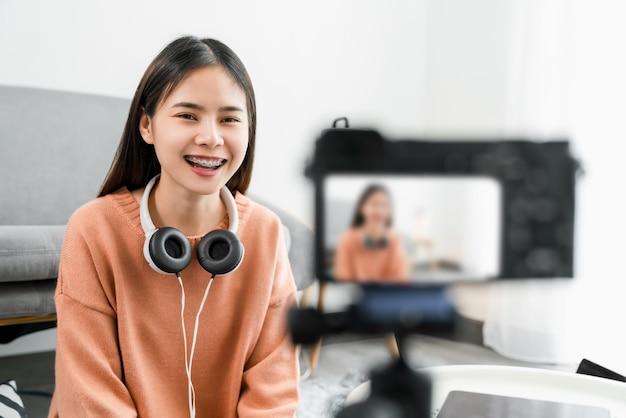Młoda piękna azjatka wpływa na vlogera podczas transmisji na żywo w internecie.