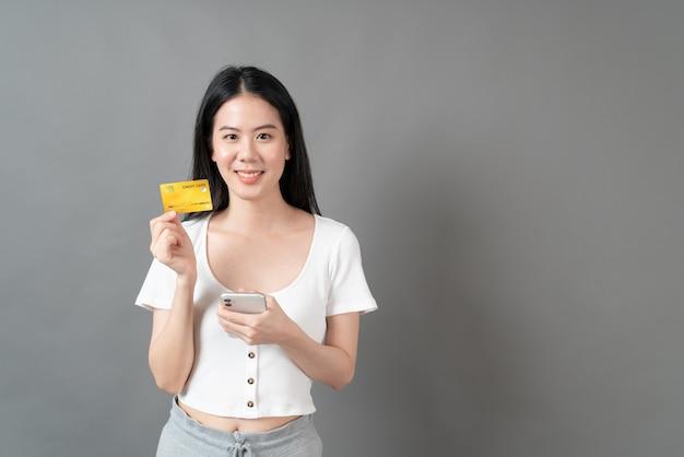 Młoda piękna azjatka z radosną buźkę i przedstawienie karty kredytowej w ręku pokazując zaufanie i pewność dokonywania płatności