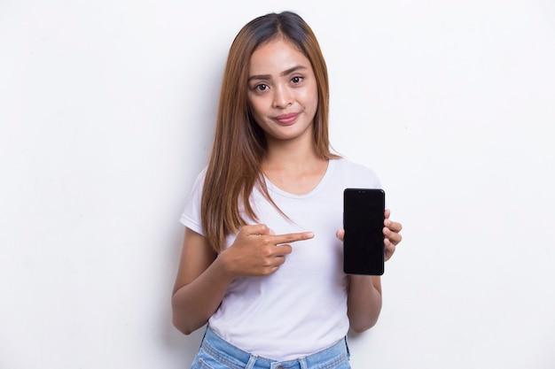 Młoda piękna azjatycka kobieta demonstruje telefon komórkowy na białym tle