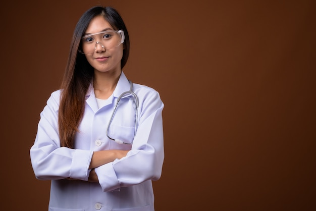Młoda piękna azjatycka kobieta lekarz noszenie okularów ochronnych ag