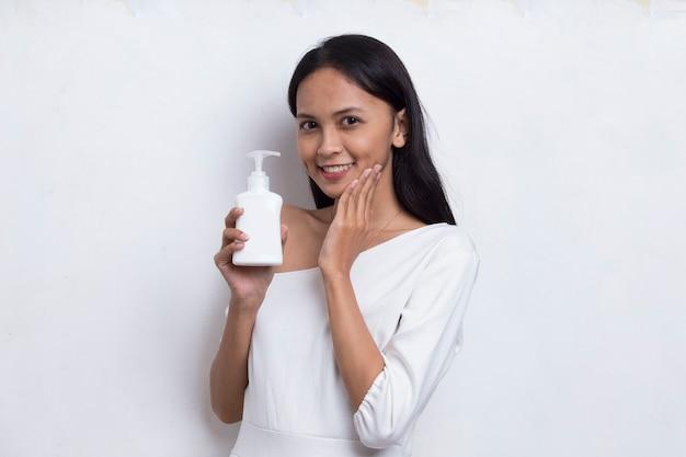 Młoda piękna azjatycka kobieta nakłada produkt do pielęgnacji skóry na twarz na białym tle