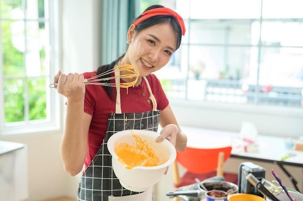 Młoda piękna azjatycka kobieta piecze w swojej kuchni, piekarni i kawiarni?