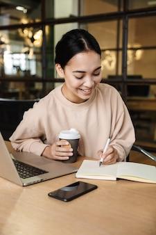 Młoda piękna azjatycka kobieta pijąca kawę i robiąca notatki podczas pracy na laptopie w biurze